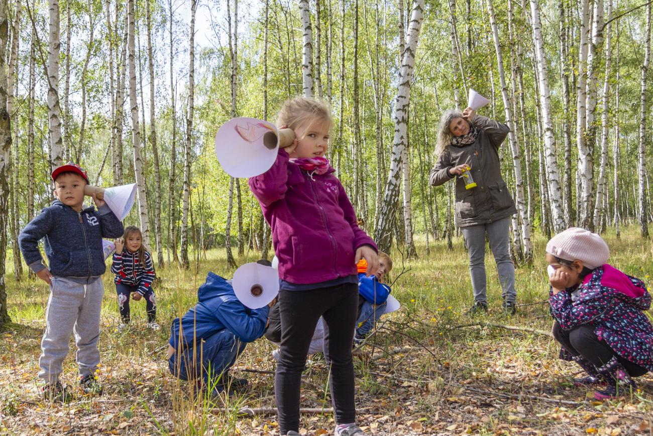 Kinder lauschen mit Hörtrichtern